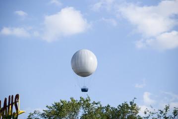 An air ballon in the sky above a city