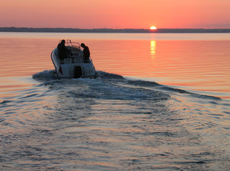 Türaufkleber Motorisierter Wassersport Speedboat sails into the sunset