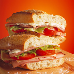 Tasty ham and tomato sandwich on a wooden table