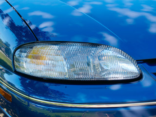Close-up of headlight on a blue car