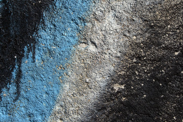 Abstract background: graffiti detail on a grainy concrete wall.
