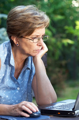 Mid adult woman working outdoors on laptop