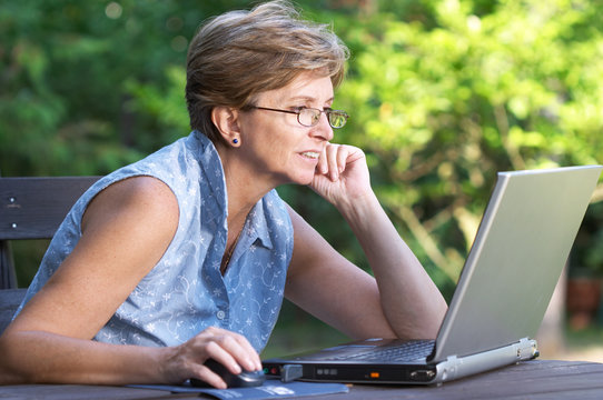 Mid adult woman working outdoors on the laptop