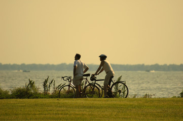a couple riding a bicycle in the park by the lake