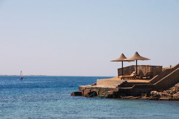 Obraz Surfing and beach with umbrellas and chaise lounges - fototapety do salonu