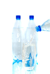 Bottles of mineral water with a glass. Isolated