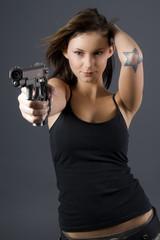 Brunette with star tatoo pointing handgun towards camera
