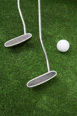 Two clubs and ball for a golf on a grass