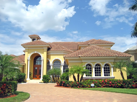 Large pink and yellow tropical house with circular driveway.