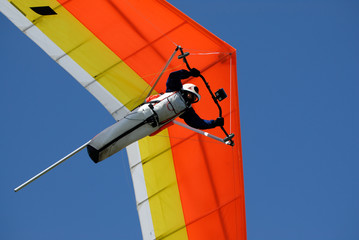 Yellow-red hang-glider under men control in the sky