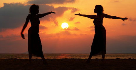 Dramatic image of two women by the ocean at sunset