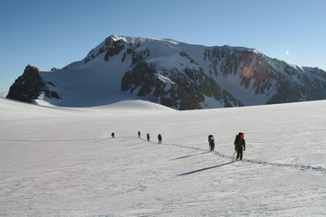group of mountaineers walking on a glacier