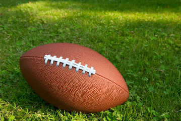 American football isolated on top of a grass background