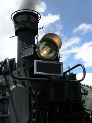 Old steam engine belching out smoke with headlight lit