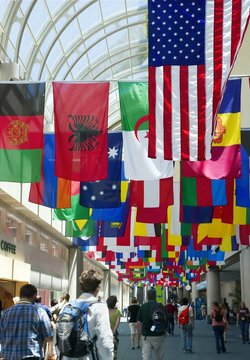Flags above a rush of people gathering for a conference