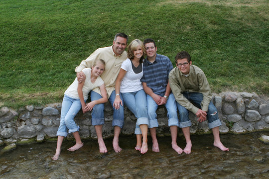 Family - Sitting with their feet in a stream.