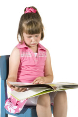 little girl is sitting and reading a book