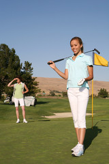 A pretty woman golfer on the putting green