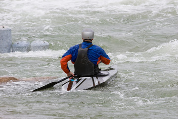 A canoeist paddling through fast running white water