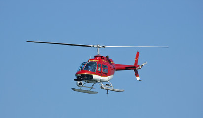 A bright red helicopter with a camera.