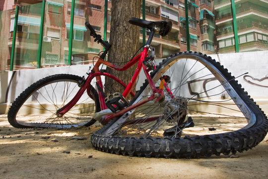 Foto cercana de una bicicleta totalmente rota en el suelo.
