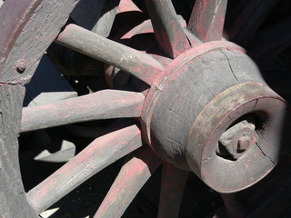 Weathered spokes on the wheel of an old covered wagon