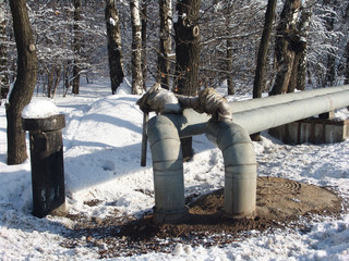 Metallic water tubes going through a nice winter forest