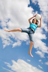 Frau mit einem Ball in ihren Händen springt auf einem Trampolin