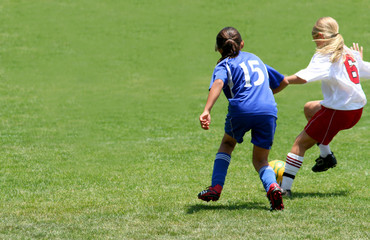 Girls playing soccer in a match
