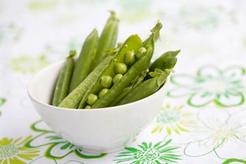 Fresh peas in white bowl, shallow focus
