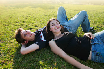 Wall Mural - Happy young couple lying on green field.