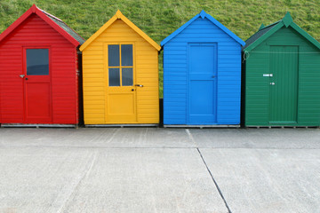 A row of four similar, but different, beach huts.