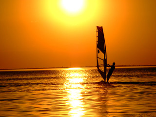 Silhouette of a windsurfer on waves of a gulf on a sunset