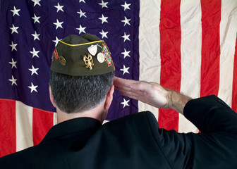 A Veteran wearing a decorated cap, saluting the American Flag
