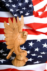 Wooden eagle statue on american flag.