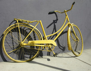 An old yellow bike leaning on a grey wall