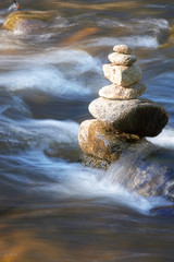 kleiner Fluss mit vielen Steinen und Wellen