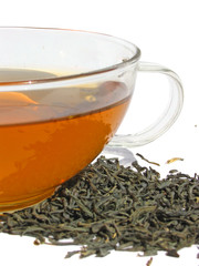 Сup of green tea with dry tea leaves on white background