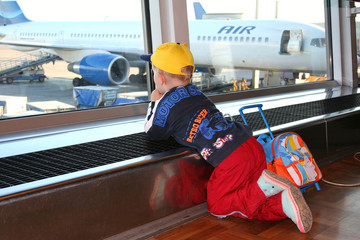 Small boy looking at airplanes. Airoport of Helsinki.