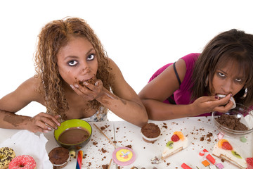 Two attractive women stuffing food into their mouths