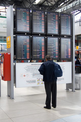 Man reading from electronic board at airport terminal