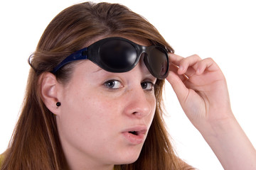 Attractive teen girl lifting sunglasses talking