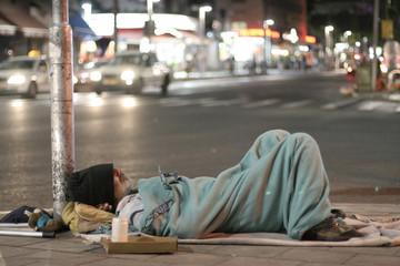 male homeless sleeping in a street