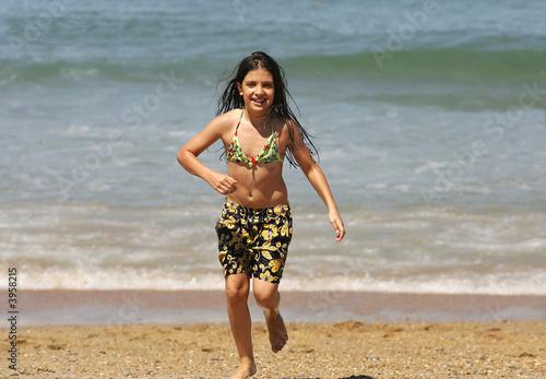 petite fille en maillot de bain qui court sur la plage photo libre de droits sur la banque d. Black Bedroom Furniture Sets. Home Design Ideas