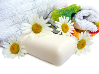 Towels, chamomiles and soap on white background