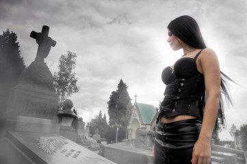 Long black haired woman in a misty cemetery