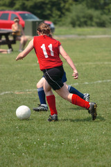 Youth Teen Chasing Soccer Ball on Field