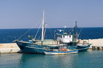 A blue and a white boat in the port at Samothraki Island.