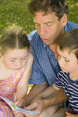 father with daughter and son reading in park