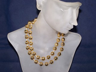 gold necklace on manniquin